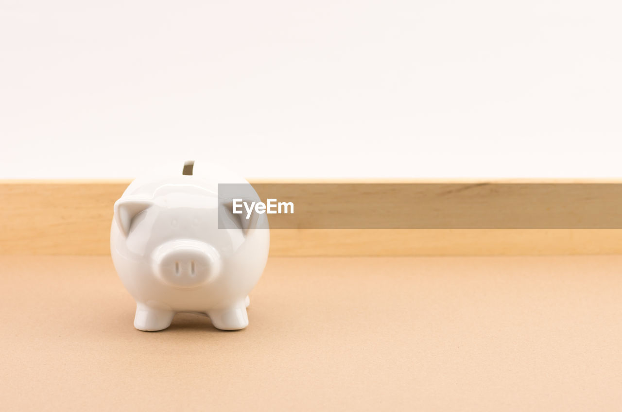 copy space, piggy bank, representation, savings, studio shot, indoors, finance, investment, no people, animal representation, wood - material, close-up, white background, white color, still life, table, business, wealth, mammal, coin bank