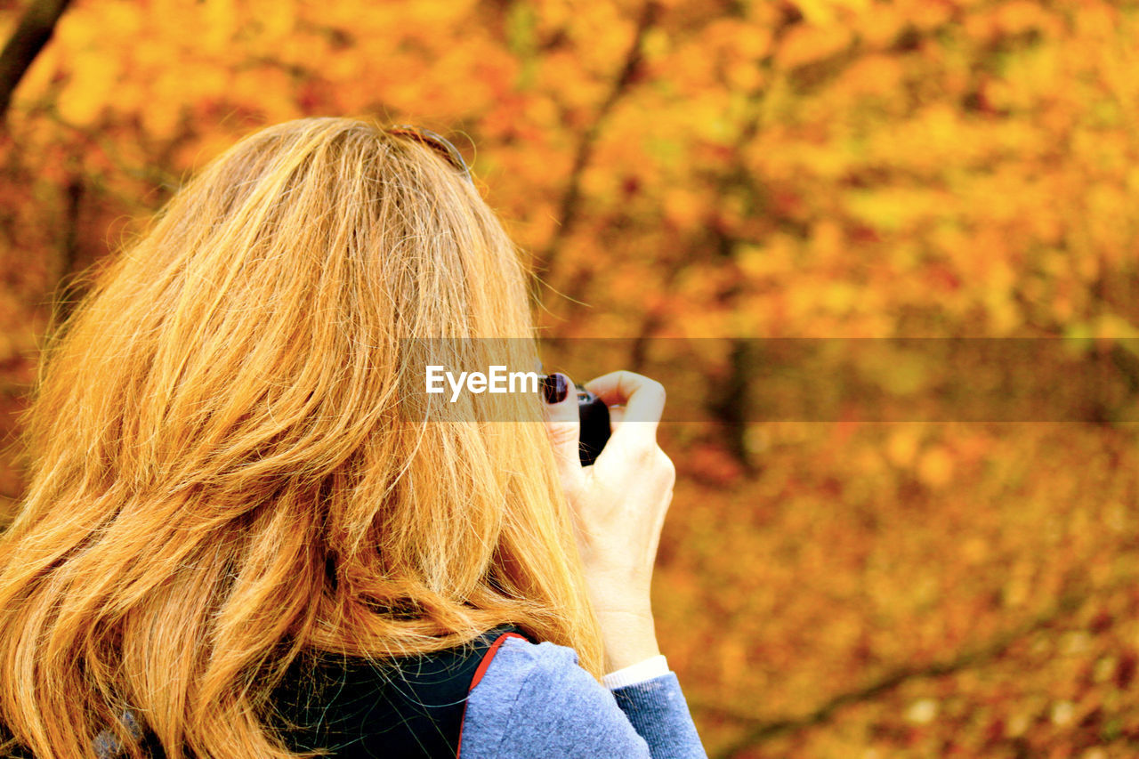 Rear View Of Mature Woman Photographing Autumn Trees At Park