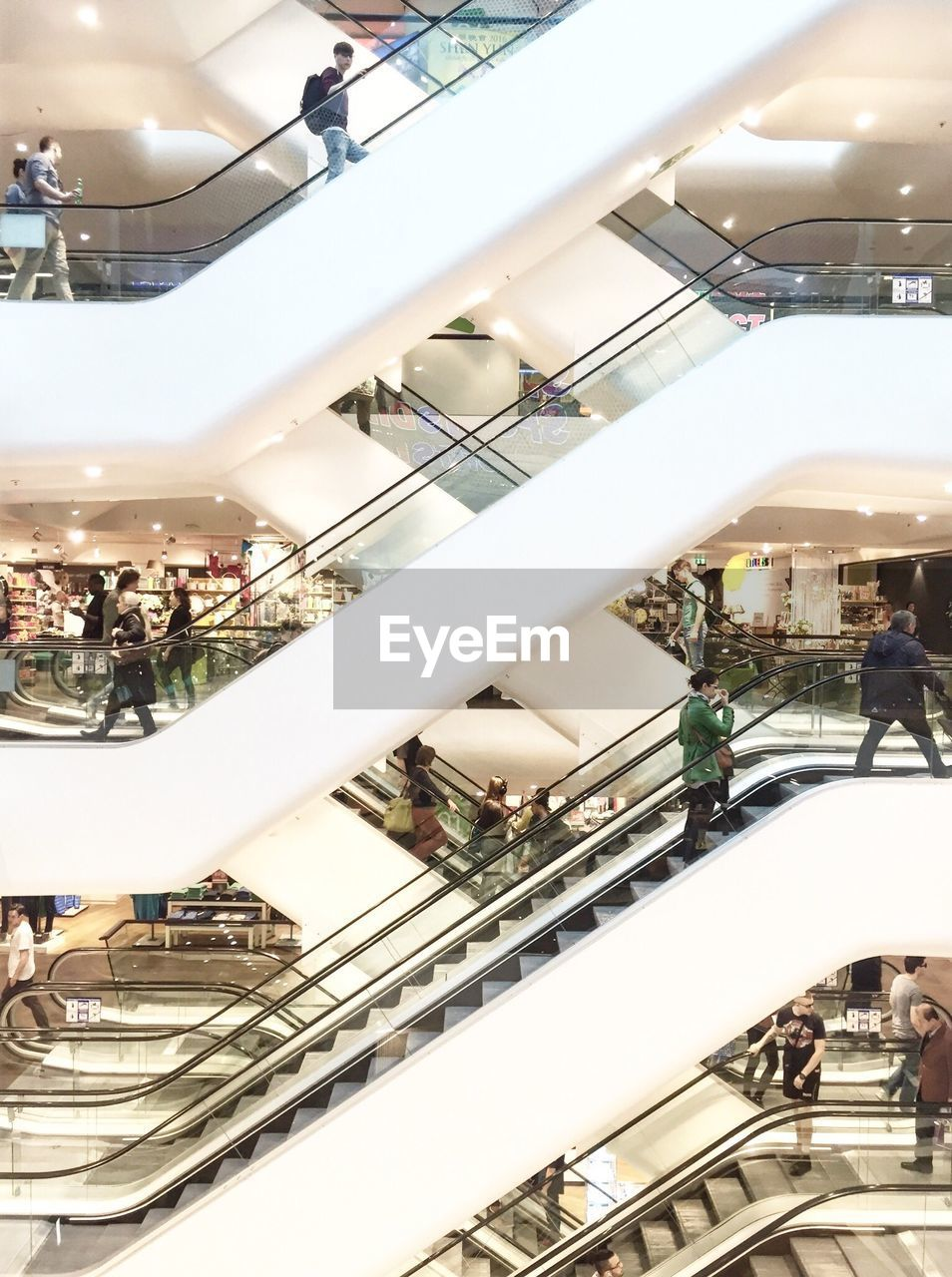 People On Escalators In Shopping Mall