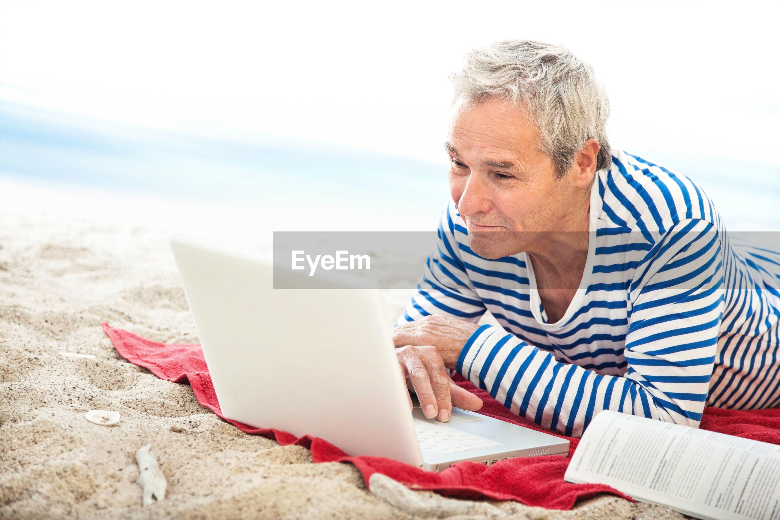 Man using laptop at beach against sky