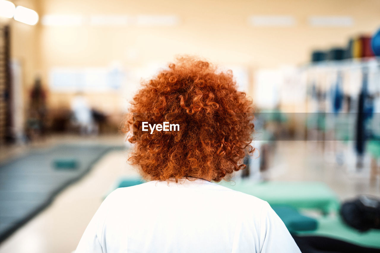 rear view, focus on foreground, real people, leisure activity, human hair, one person, headshot, indoors, women, lifestyles, curly hair, day, close-up, young women, young adult