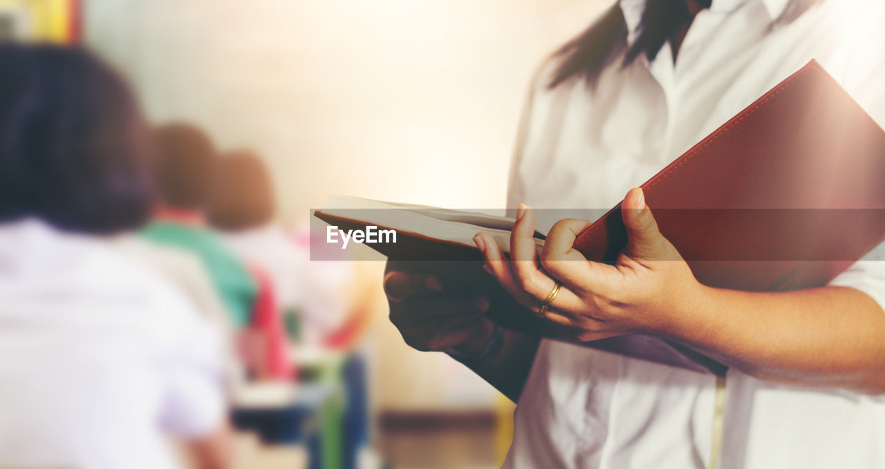 Midsection of teacher with book standing in classroom