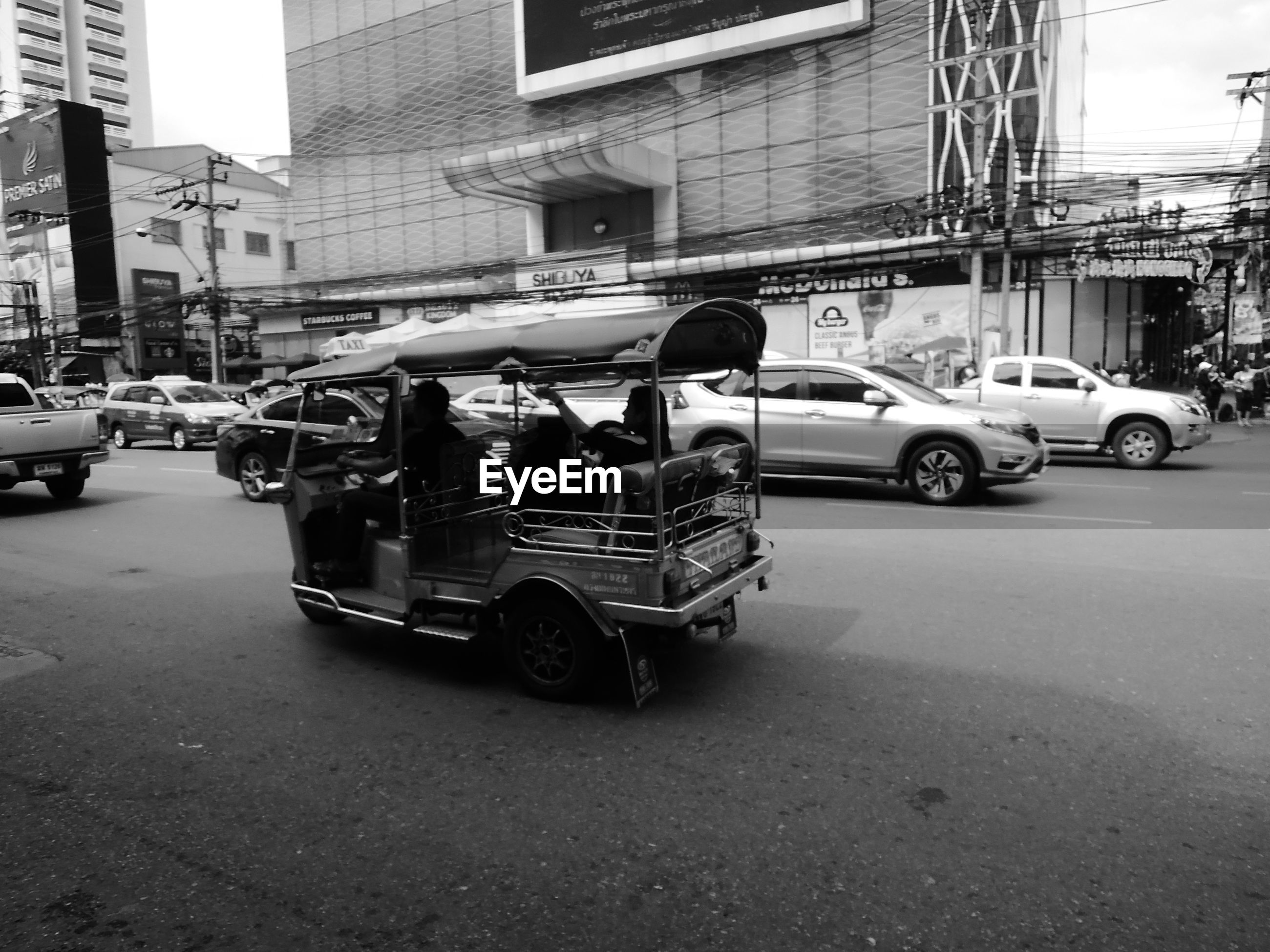 MAN ON CAR ON STREET IN CITY