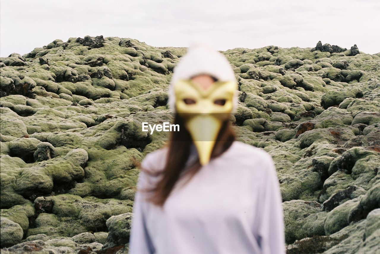 Close-Up Of Woman Wearing Mask Against Sky