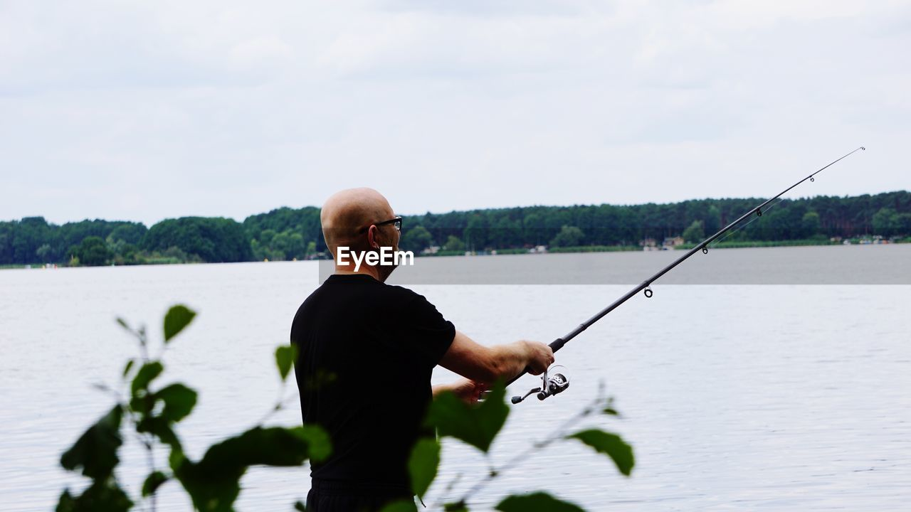 Bald Man Fishing In Lake Against Sky