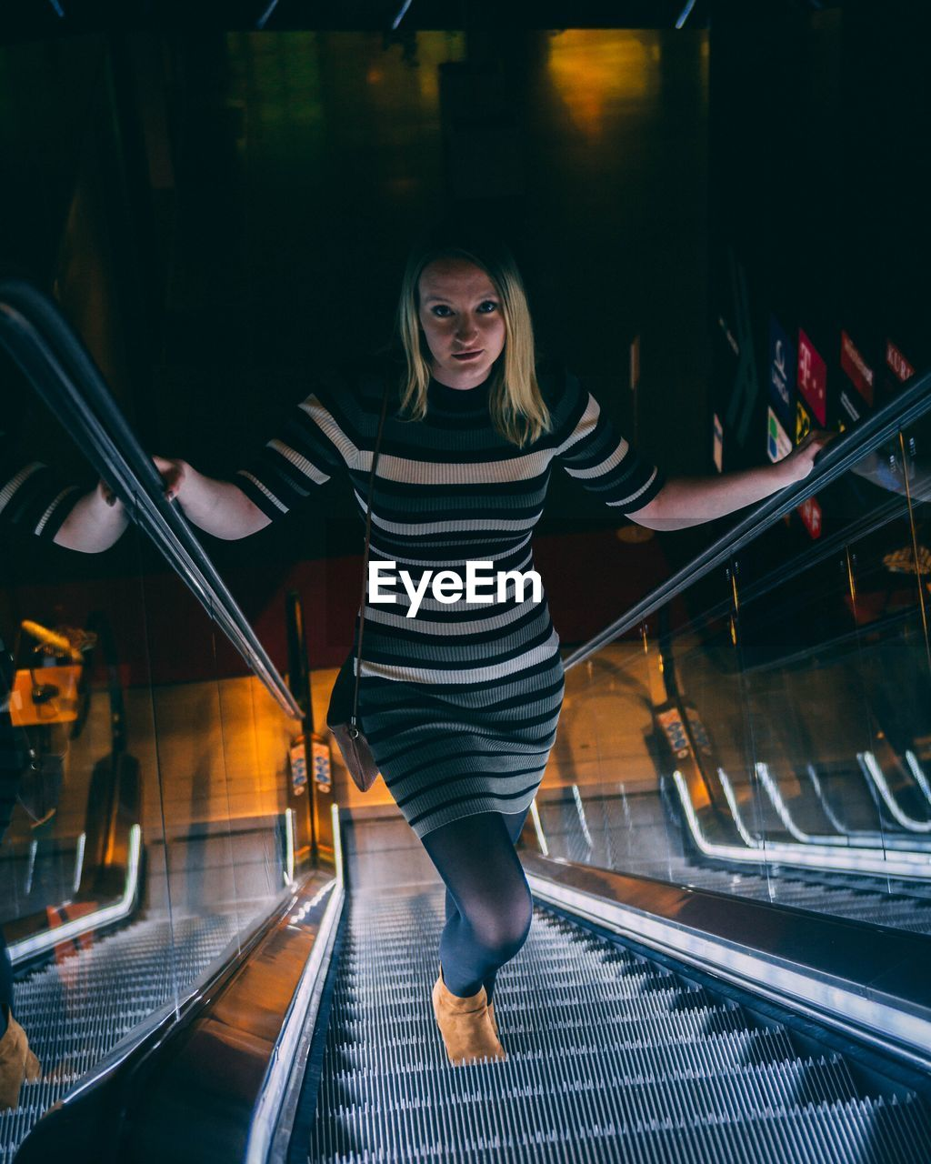 Full Length Portrait Of Young Woman Standing On Escalator