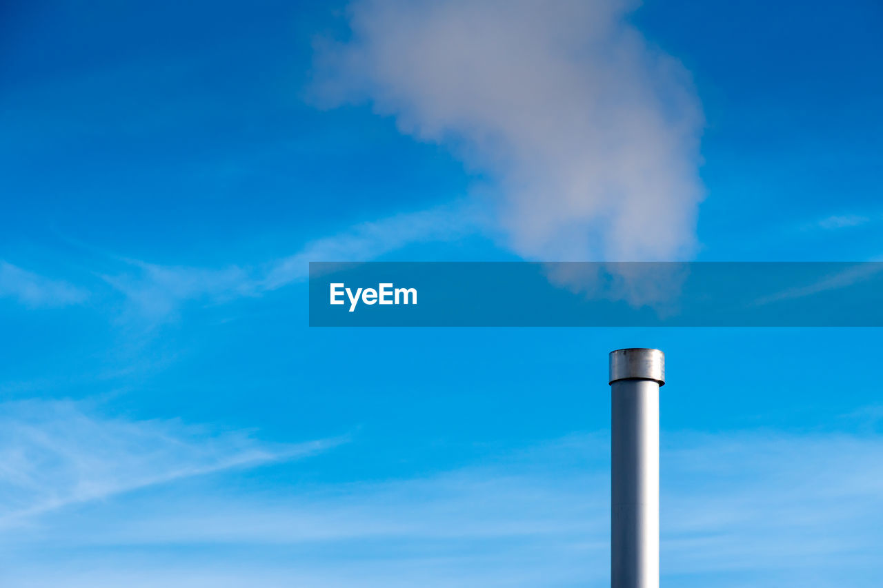 sky, factory, pollution, cloud - sky, smoke stack, emitting, environmental issues, smoke - physical structure, industry, blue, air pollution, low angle view, environment, day, nature, environmental damage, no people, building exterior, outdoors, chimney, fumes