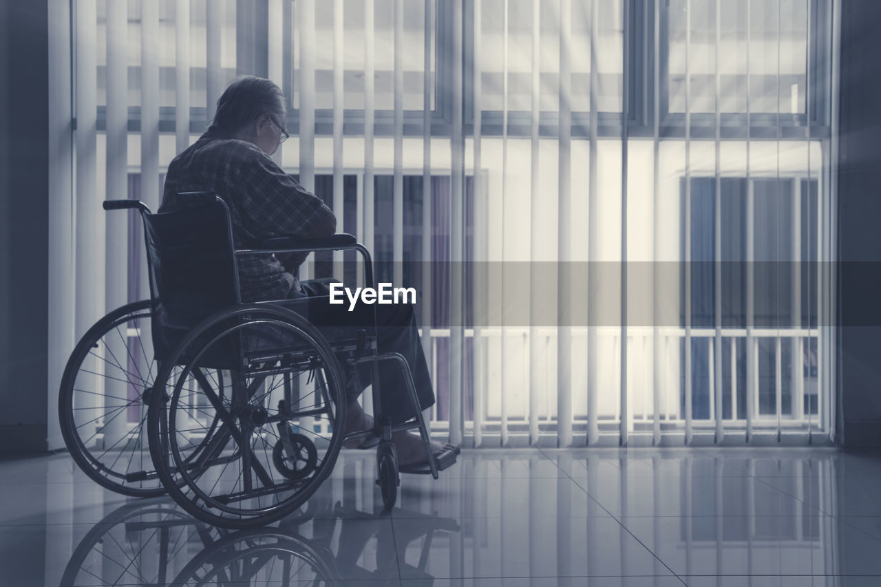 Rear view of man sitting in wheelchair by window