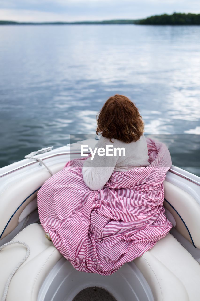 Rear view of person sitting on boat in sea