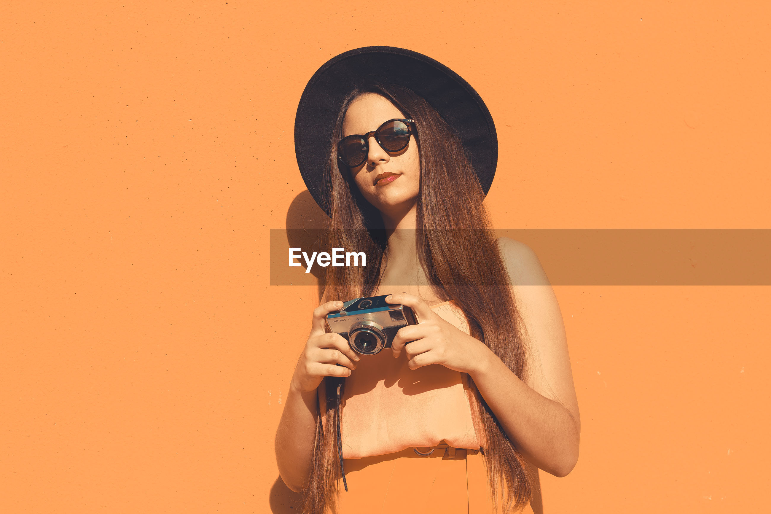Portrait of young woman wearing sunglasses and hat while holding camera against orange background