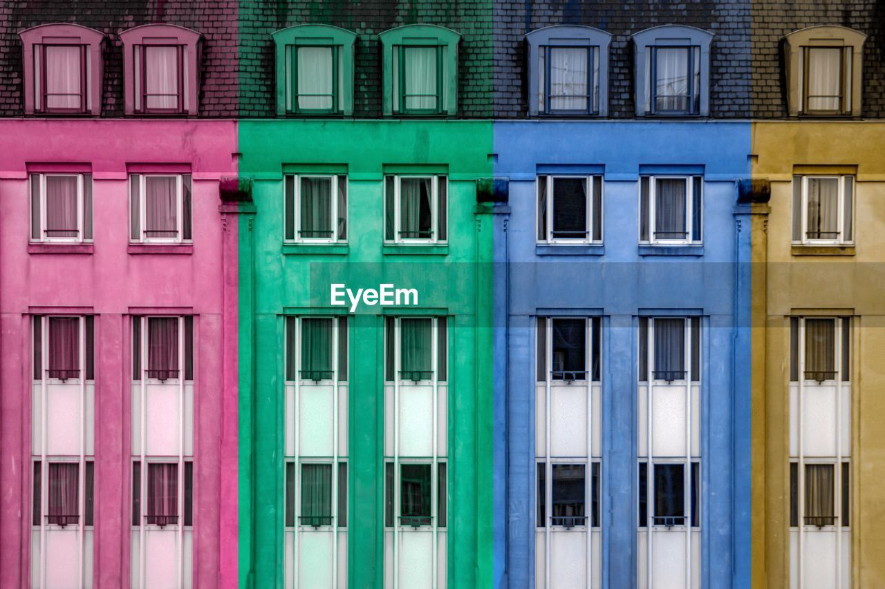 window, building exterior, architecture, built structure, building, no people, residential district, green color, in a row, day, full frame, blue, side by side, pink color, multi colored, city, glass - material, outdoors, entrance, backgrounds, turquoise colored