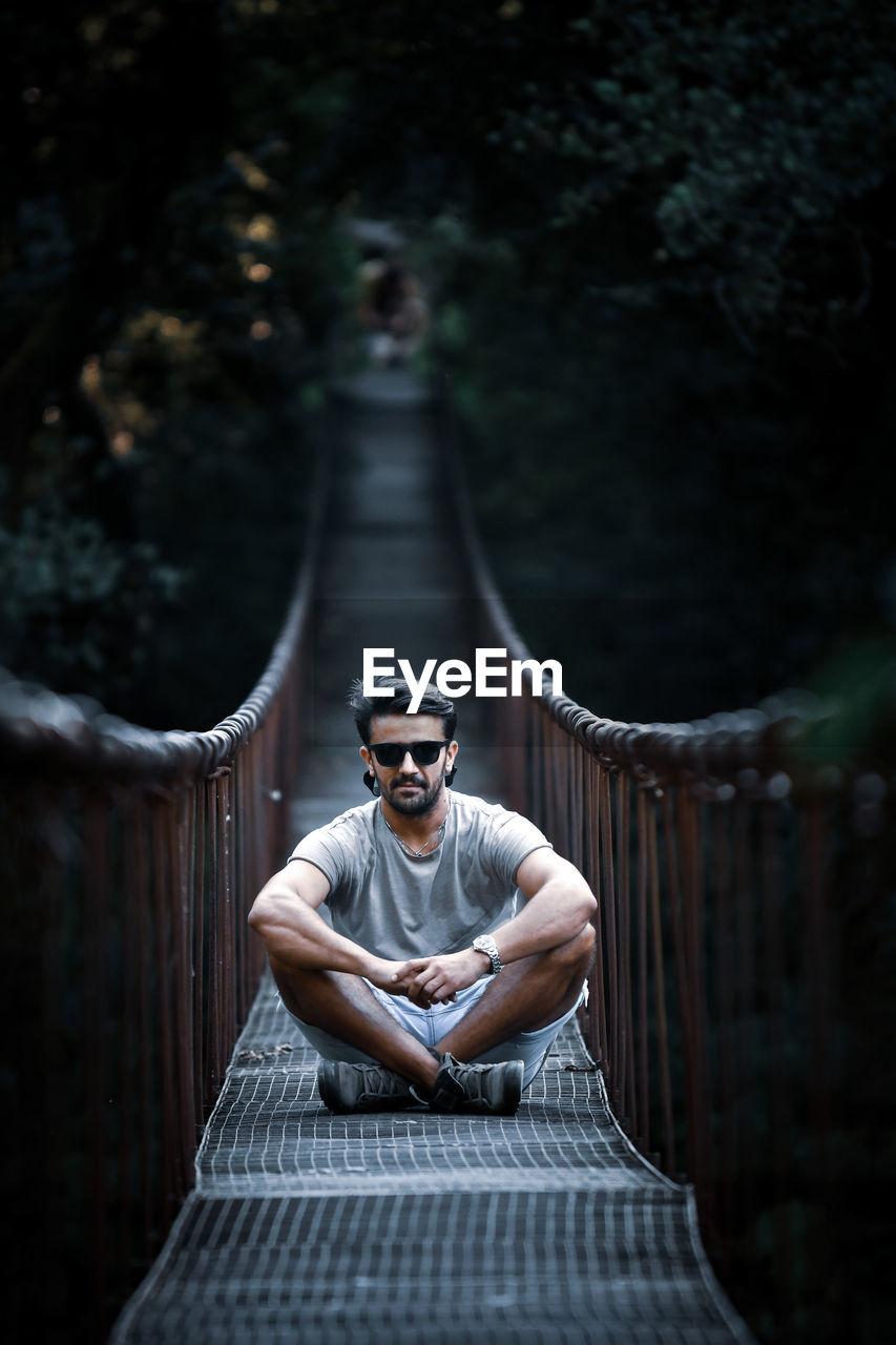 Portrait of man in sunglasses sitting on footbridge