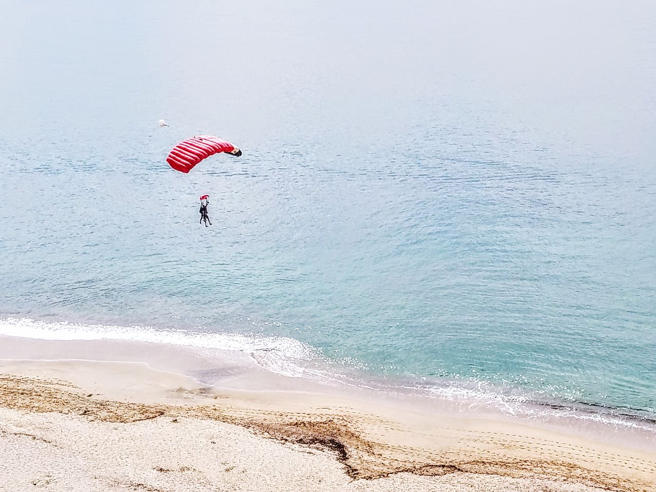 People paragliding over beach