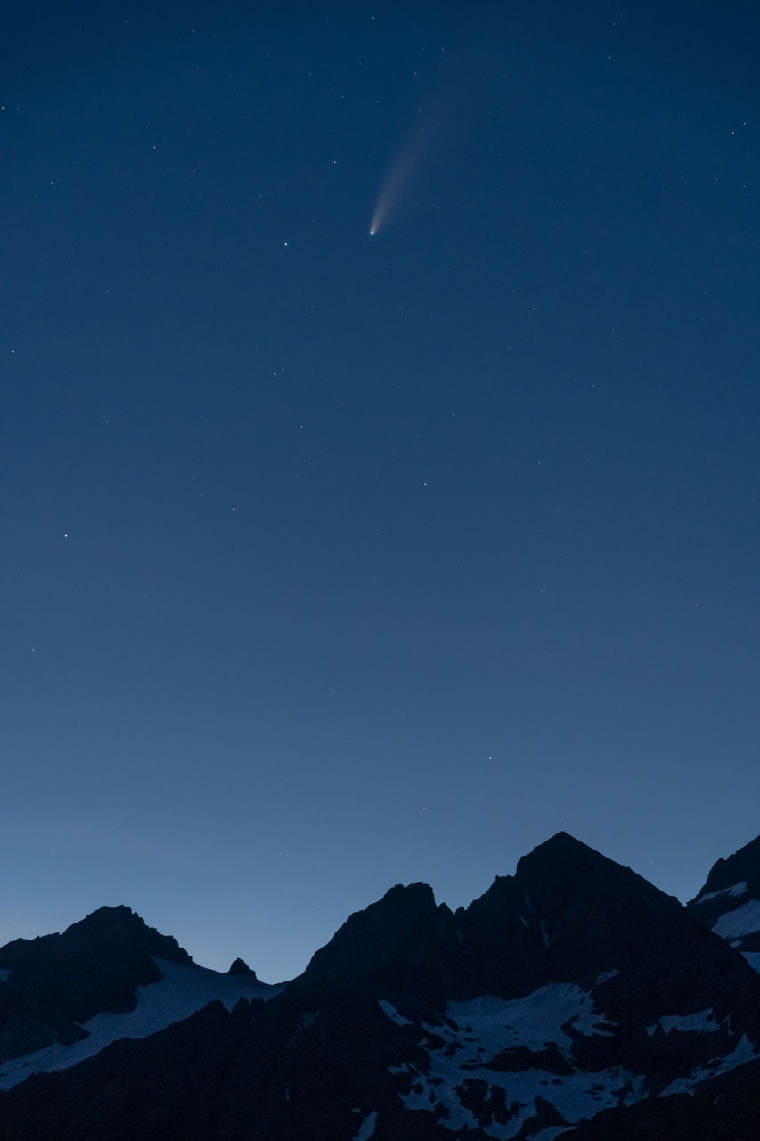Scenic view of snowcapped mountains against sky at night and comet neowise