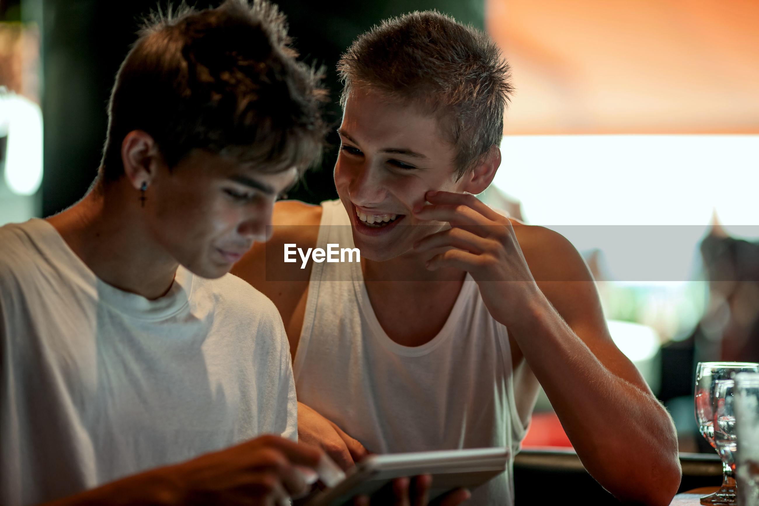 Smiling friends using digital tablet in restaurant