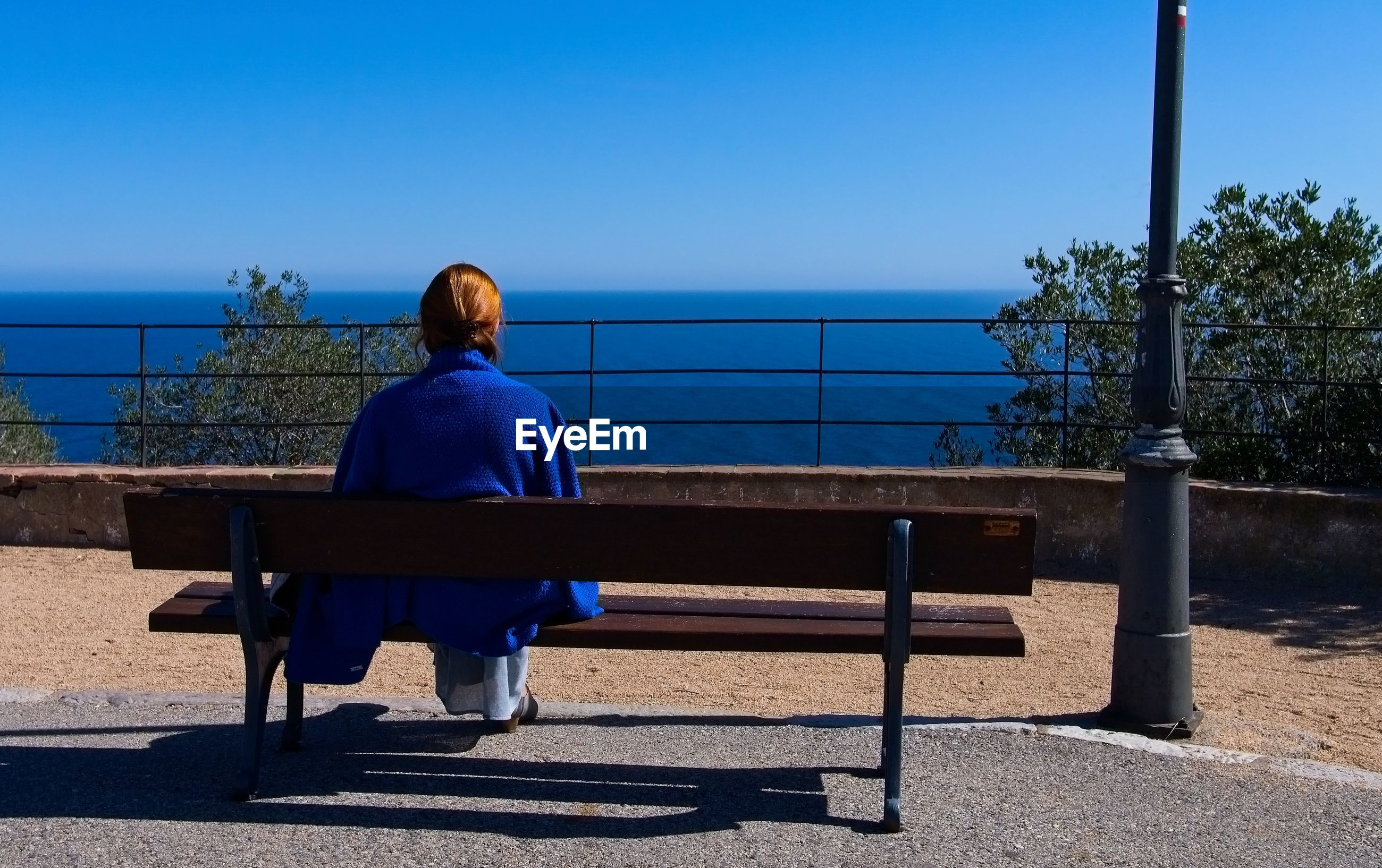 REAR VIEW OF WOMAN SITTING ON BENCH AGAINST SEA