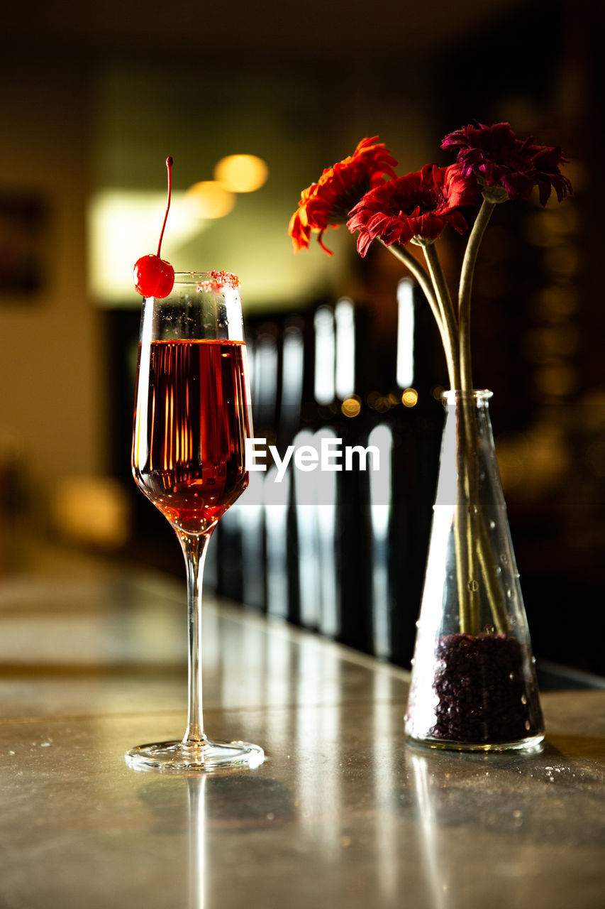 glass, alcohol, drink, table, food and drink, refreshment, red, freshness, wineglass, glass - material, wine, close-up, indoors, focus on foreground, flowering plant, flower, vase, no people, still life, transparent, red wine, bar counter