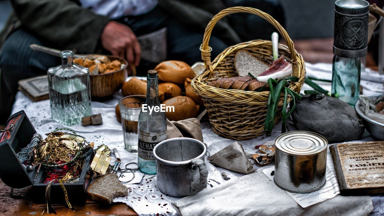 container, basket, food, market, food and drink, real people, focus on foreground, one person, day, large group of objects, freshness, men, choice, market stall, variation, retail, table, wicker, incidental people, vegetable
