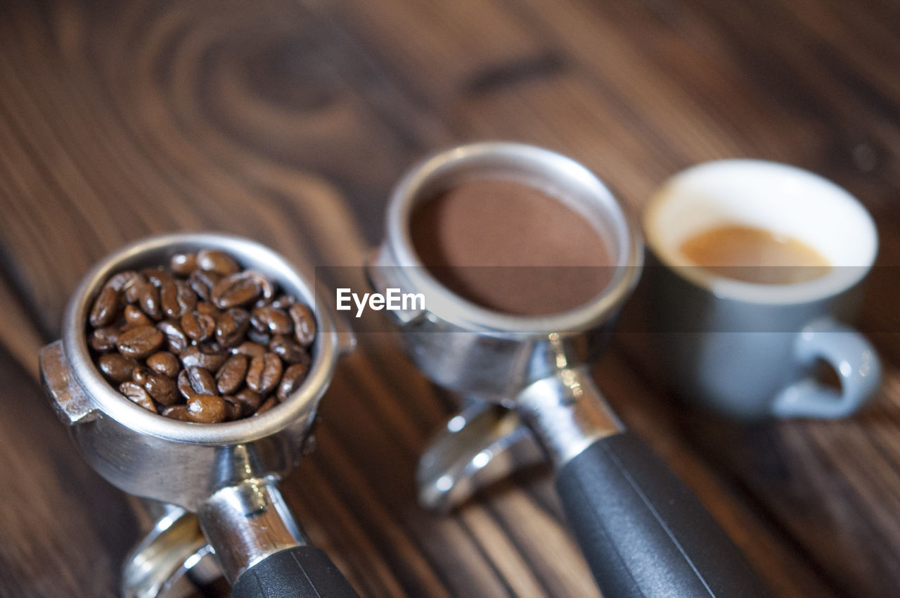 High Angle View Of Coffee In Containers On Wooden Table In Cafe