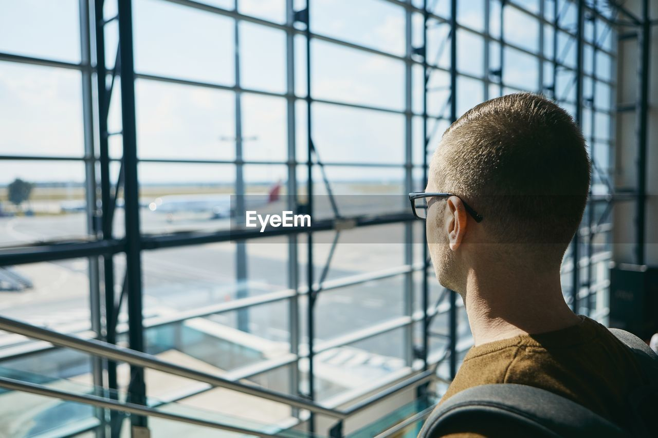 Man Looking Airplane Through Window
