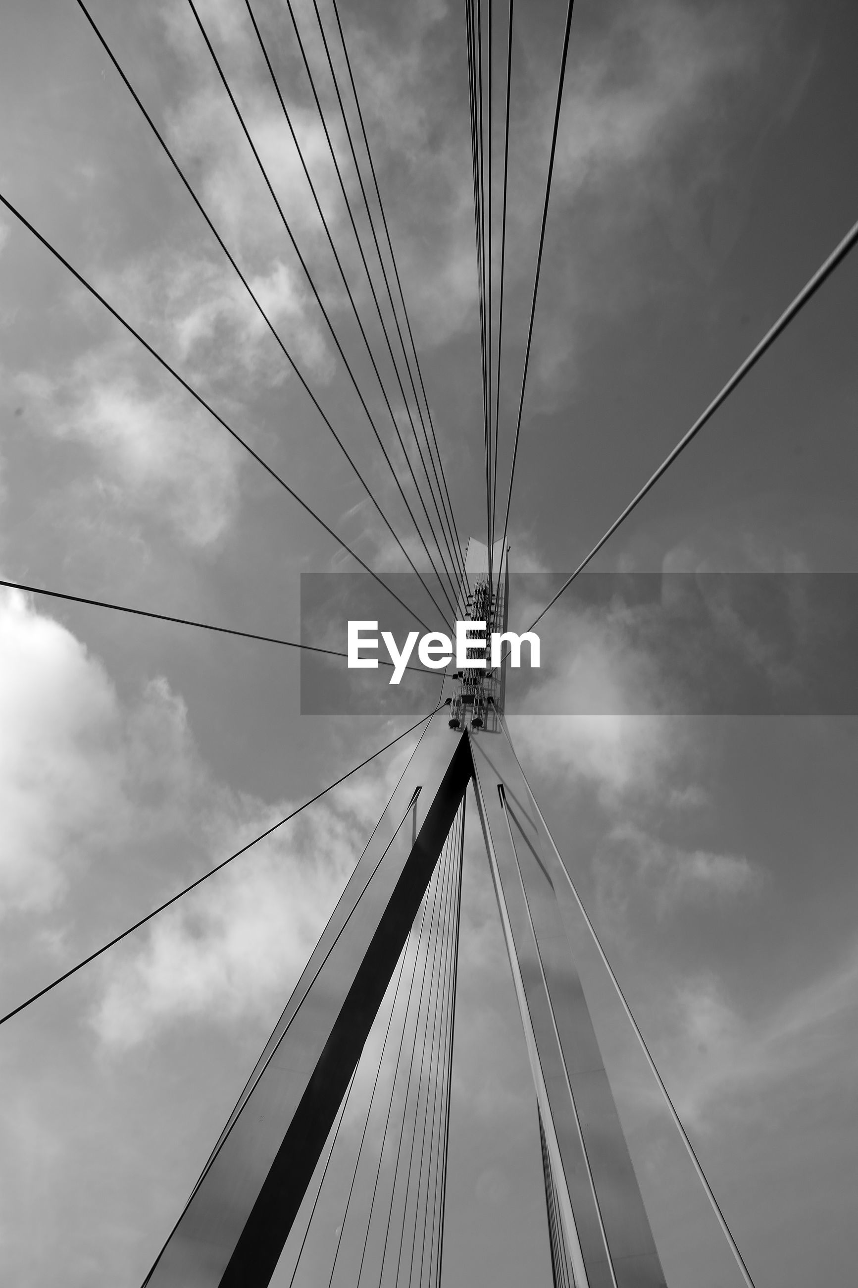 LOW ANGLE VIEW OF BRIDGE CABLES AGAINST CLOUDY SKY