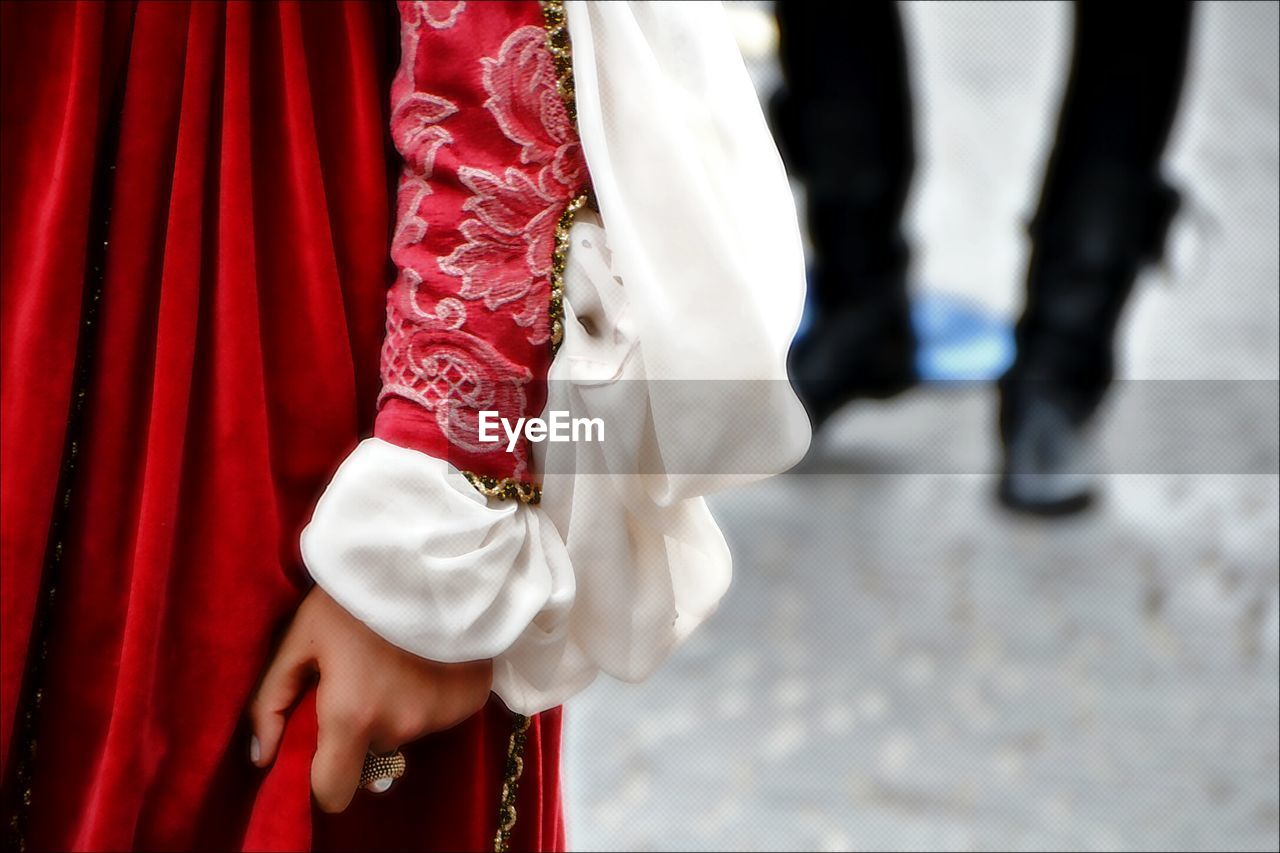 red, real people, traditional clothing, women, men, day, outdoors, human hand