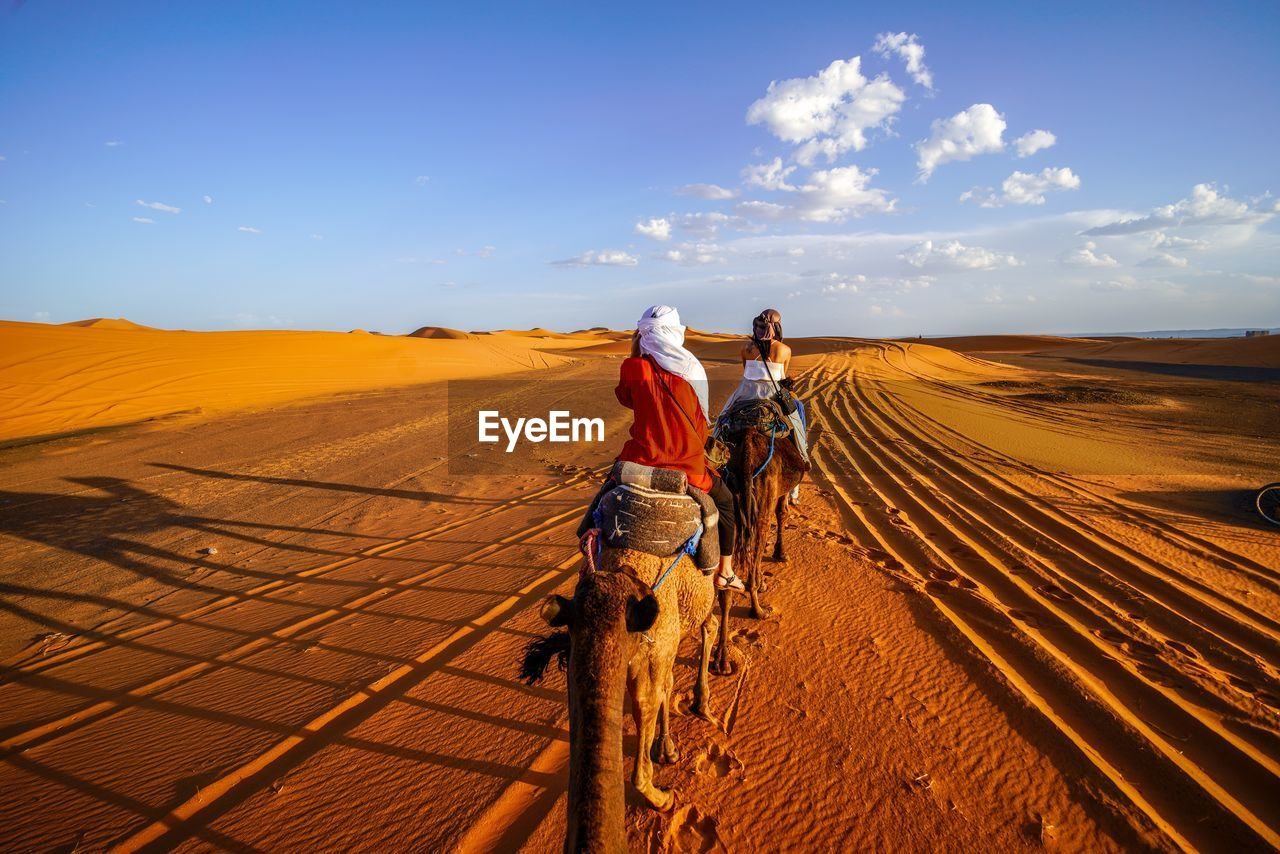 sky, real people, rear view, landscape, environment, lifestyles, desert, scenics - nature, land, two people, full length, men, nature, people, beauty in nature, women, leisure activity, cloud - sky, sunlight, casual clothing, climate, arid climate, outdoors