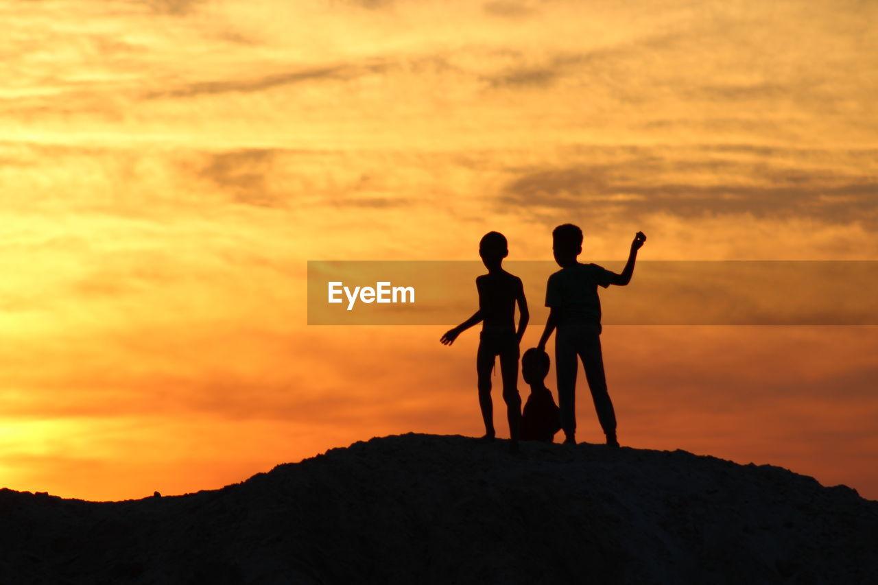 Silhouette Of Children Standing Against Orange Sky