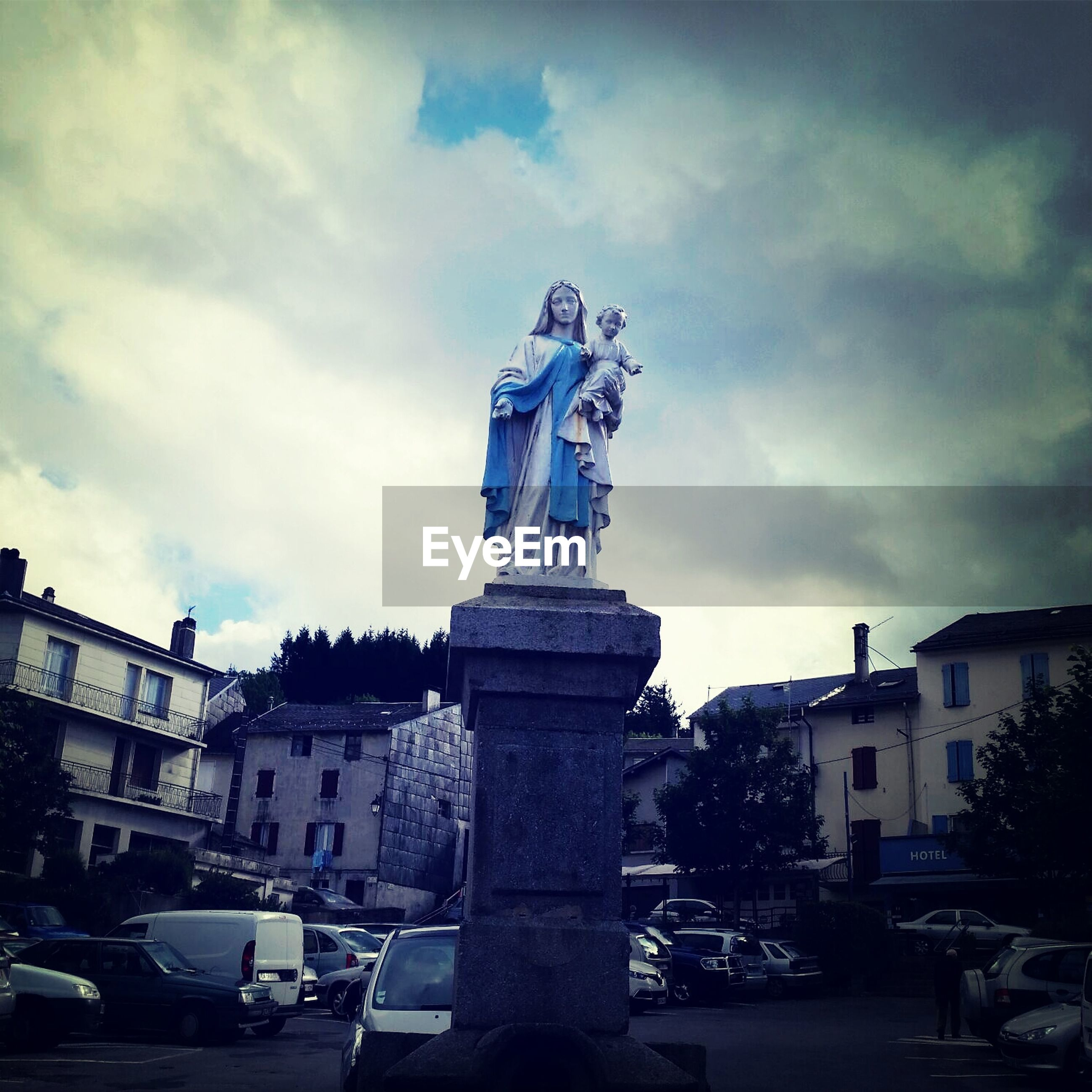 Low angle view of virgin mary statue in city against cloudy sky