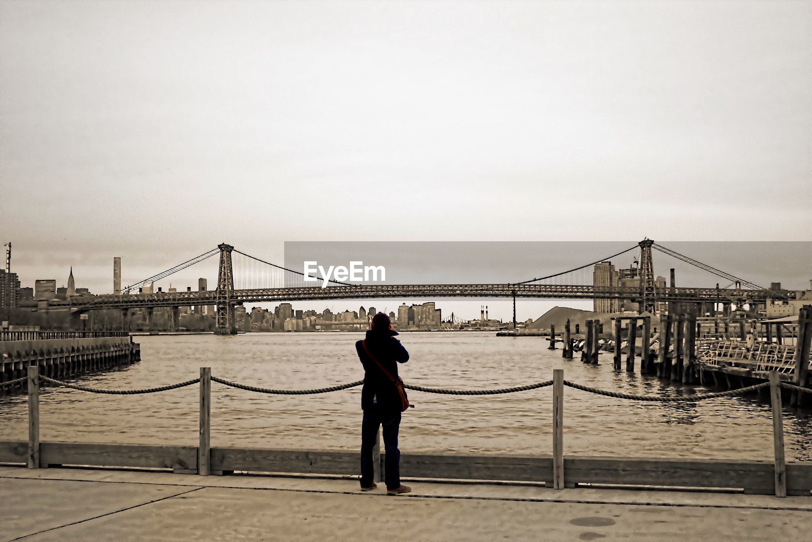 Rear view of man standing in front of williamsburg bridge over east river