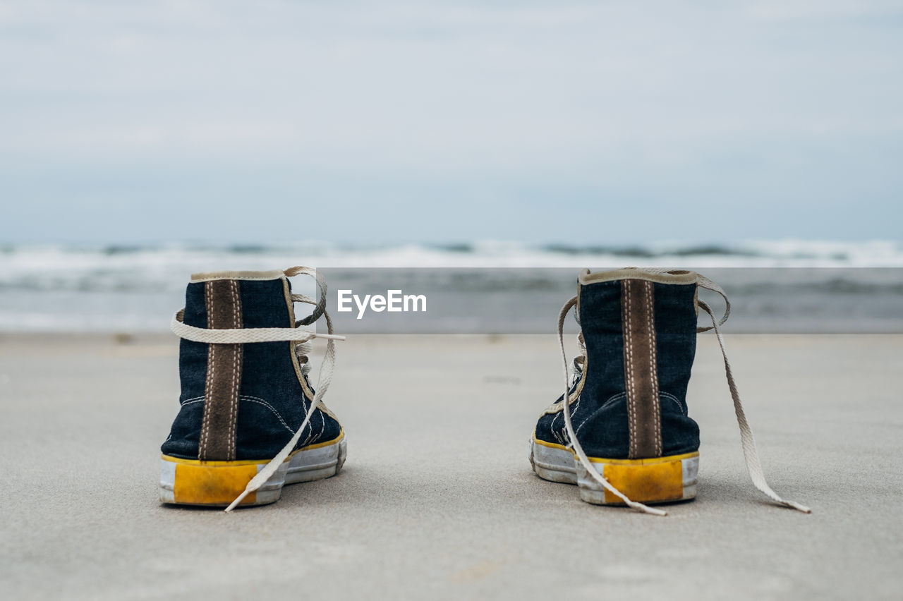 Close-Up Of Canvas Shoes On Shore At Beach