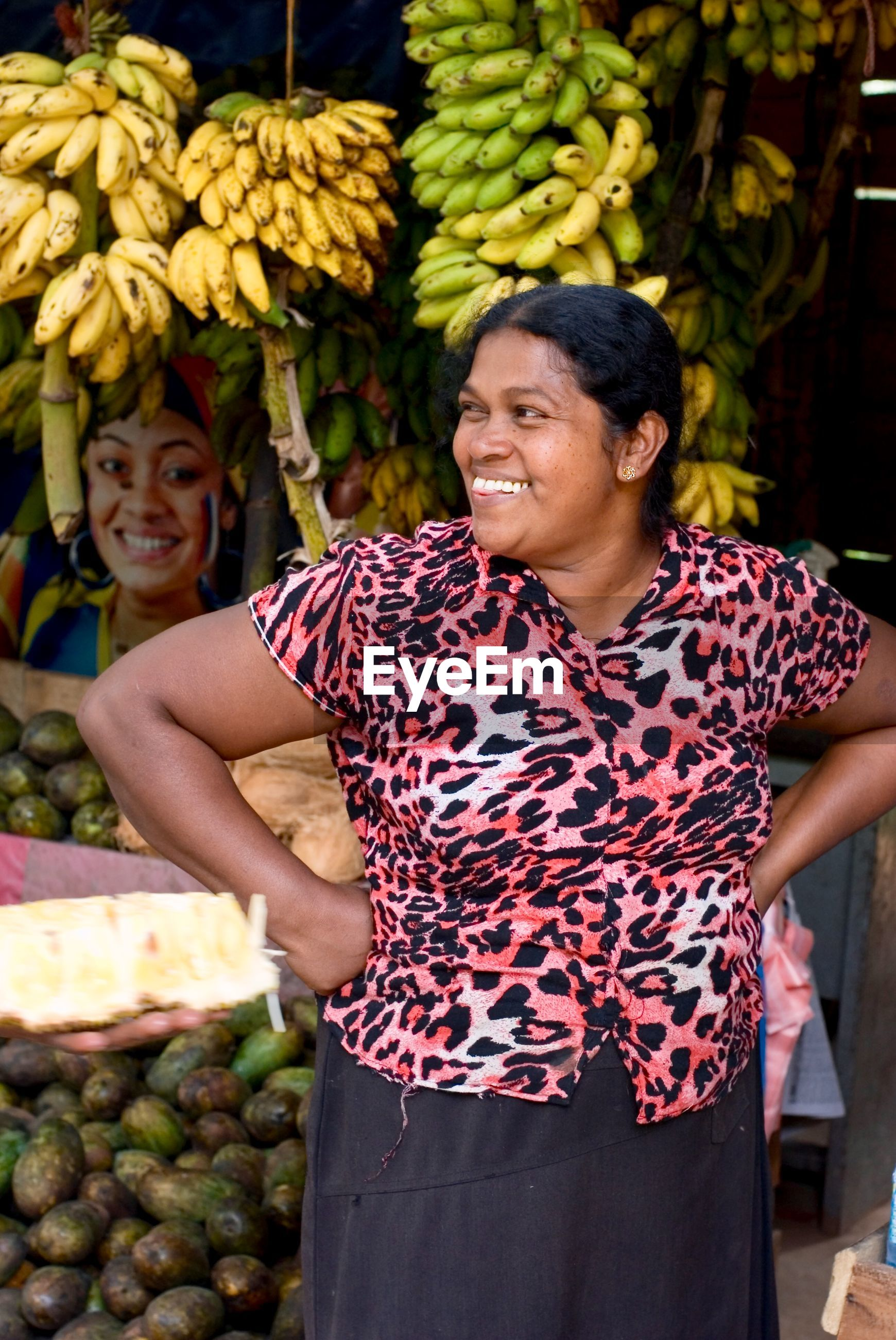 SMILING YOUNG WOMAN WITH FRUITS AT MARKET