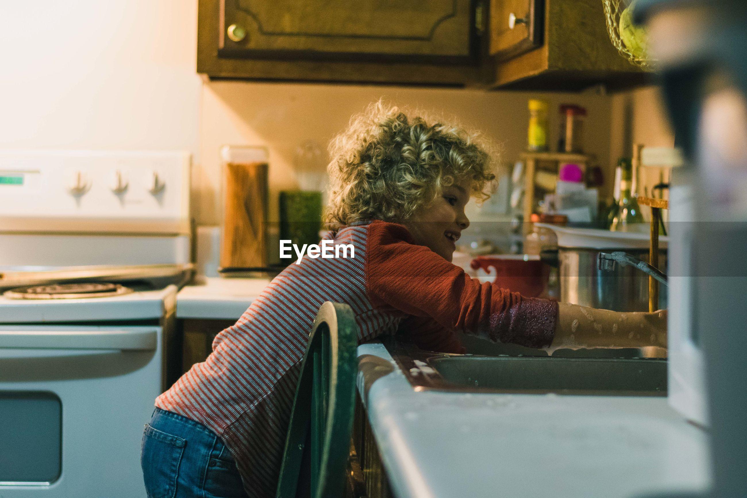 Close-up of boy washing hands in kitchen sink
