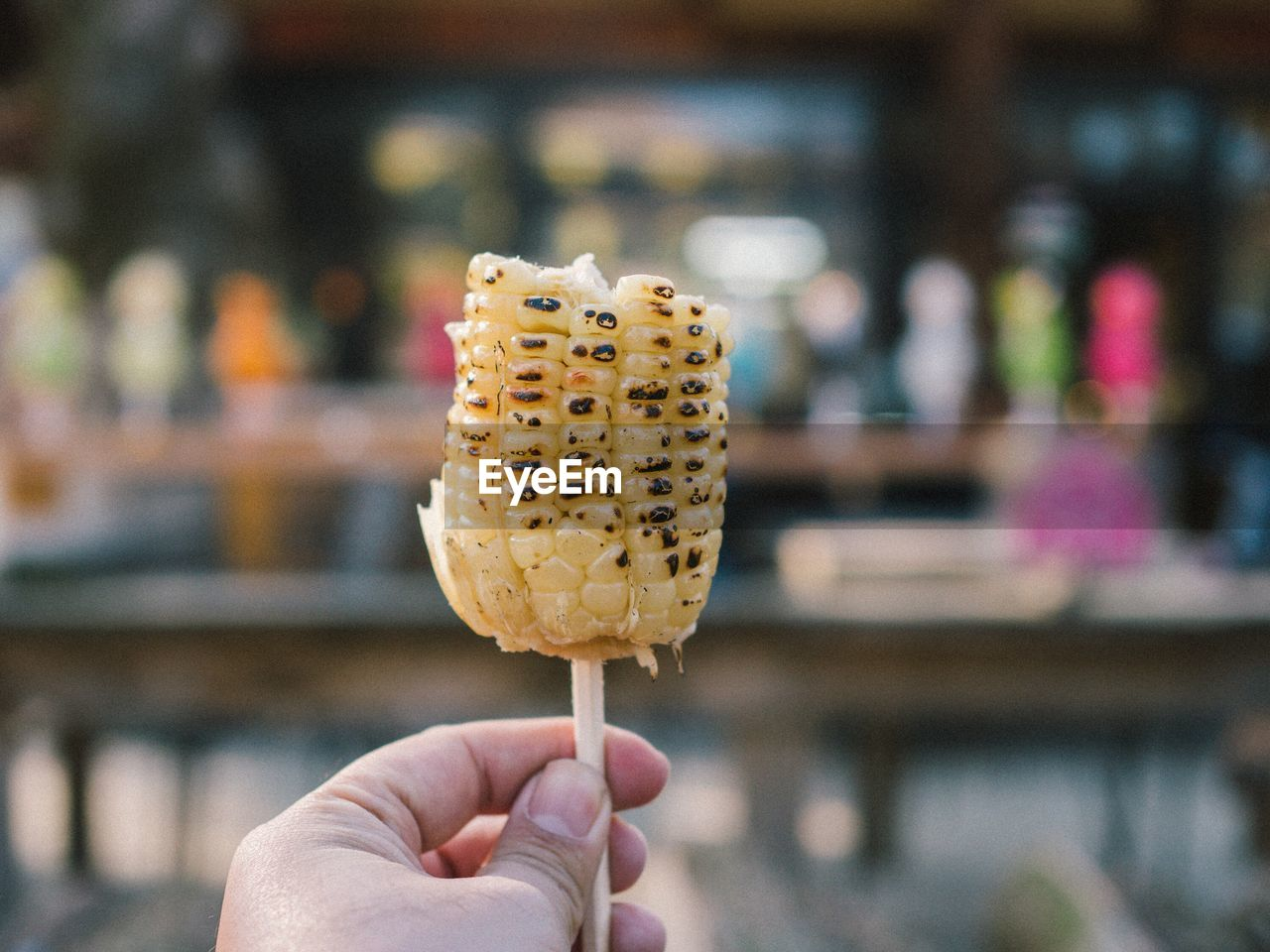 Close-Up Of Hand Holding Corn On Stick