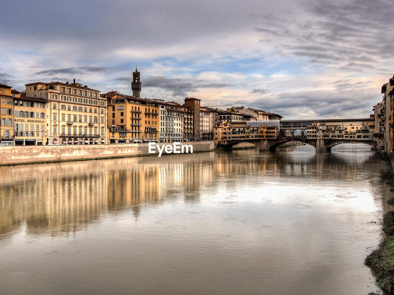 Ponte Vecchio Over Arno River Against Cloudy Sky