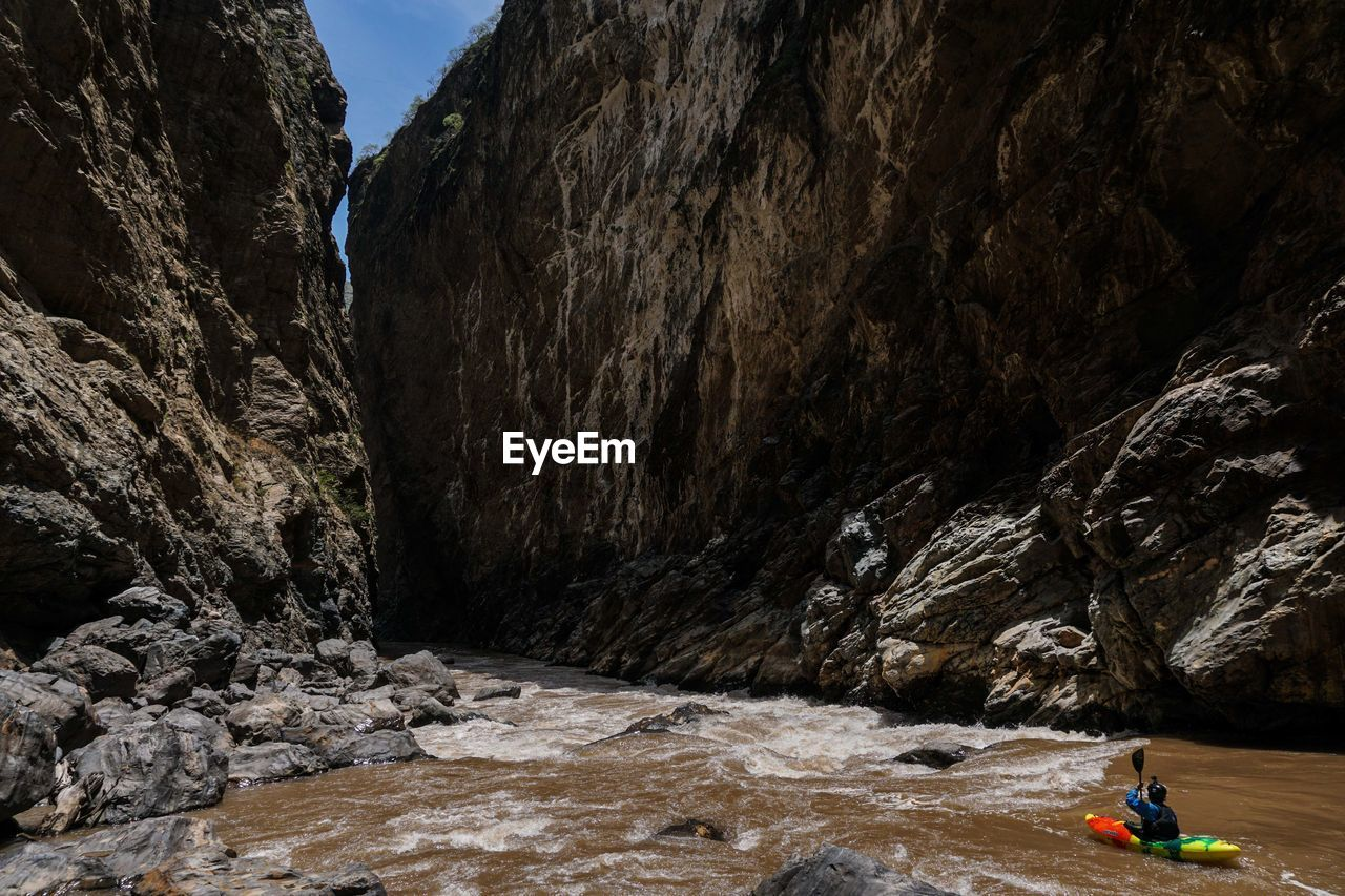 High angle view of man kayaking on river against rock formations