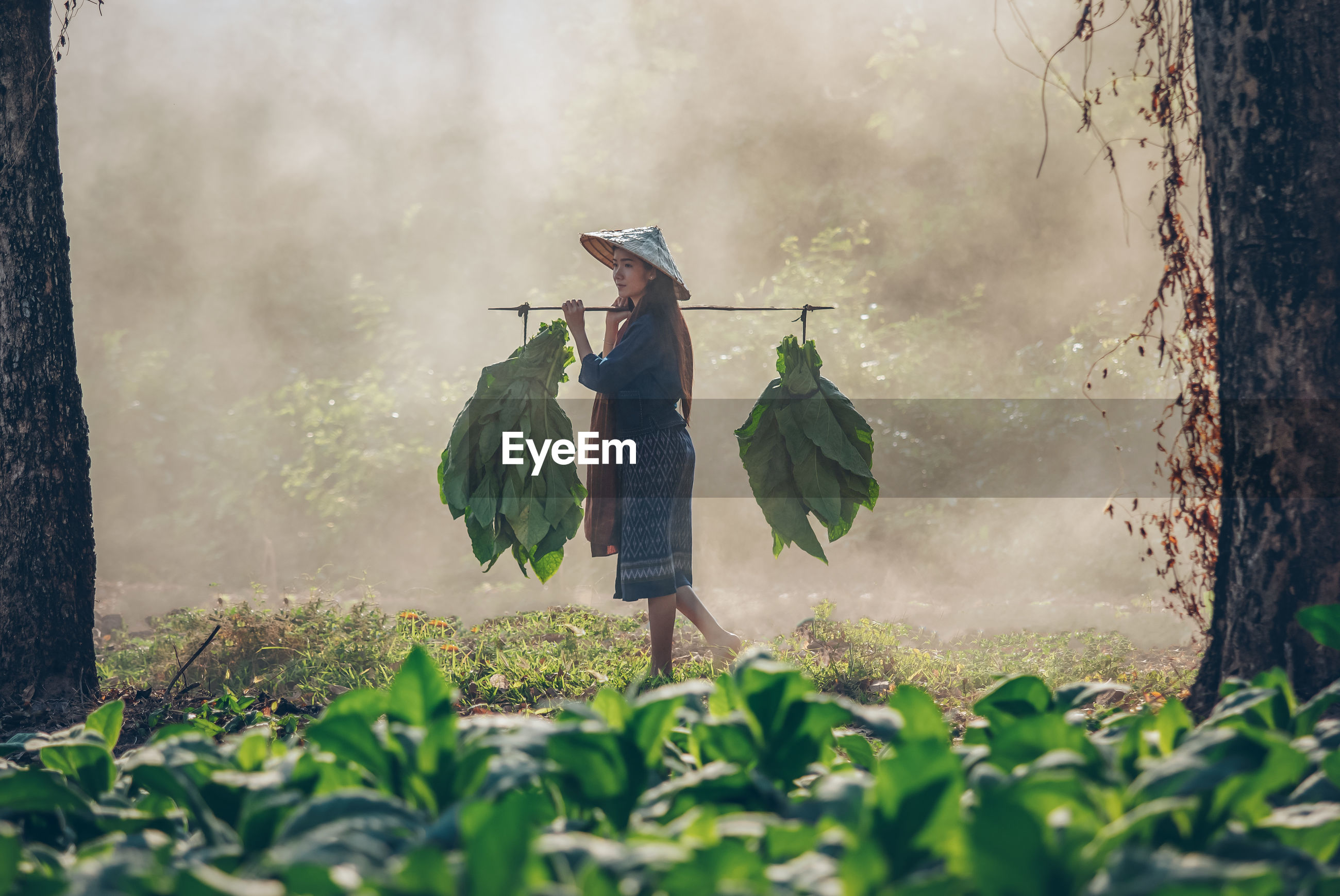 WOMAN STANDING AGAINST PLANTS