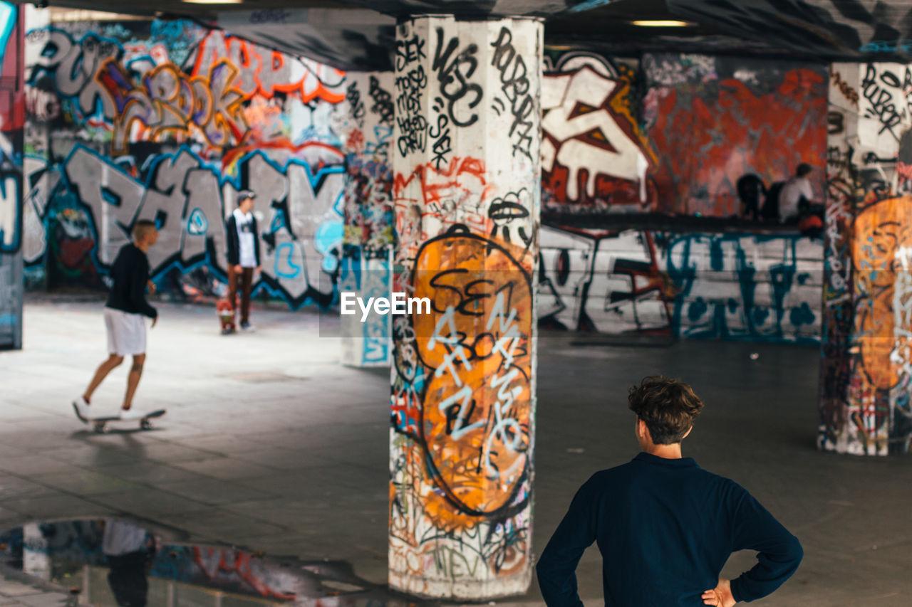 Young Men At Graffiti Skateboard Park
