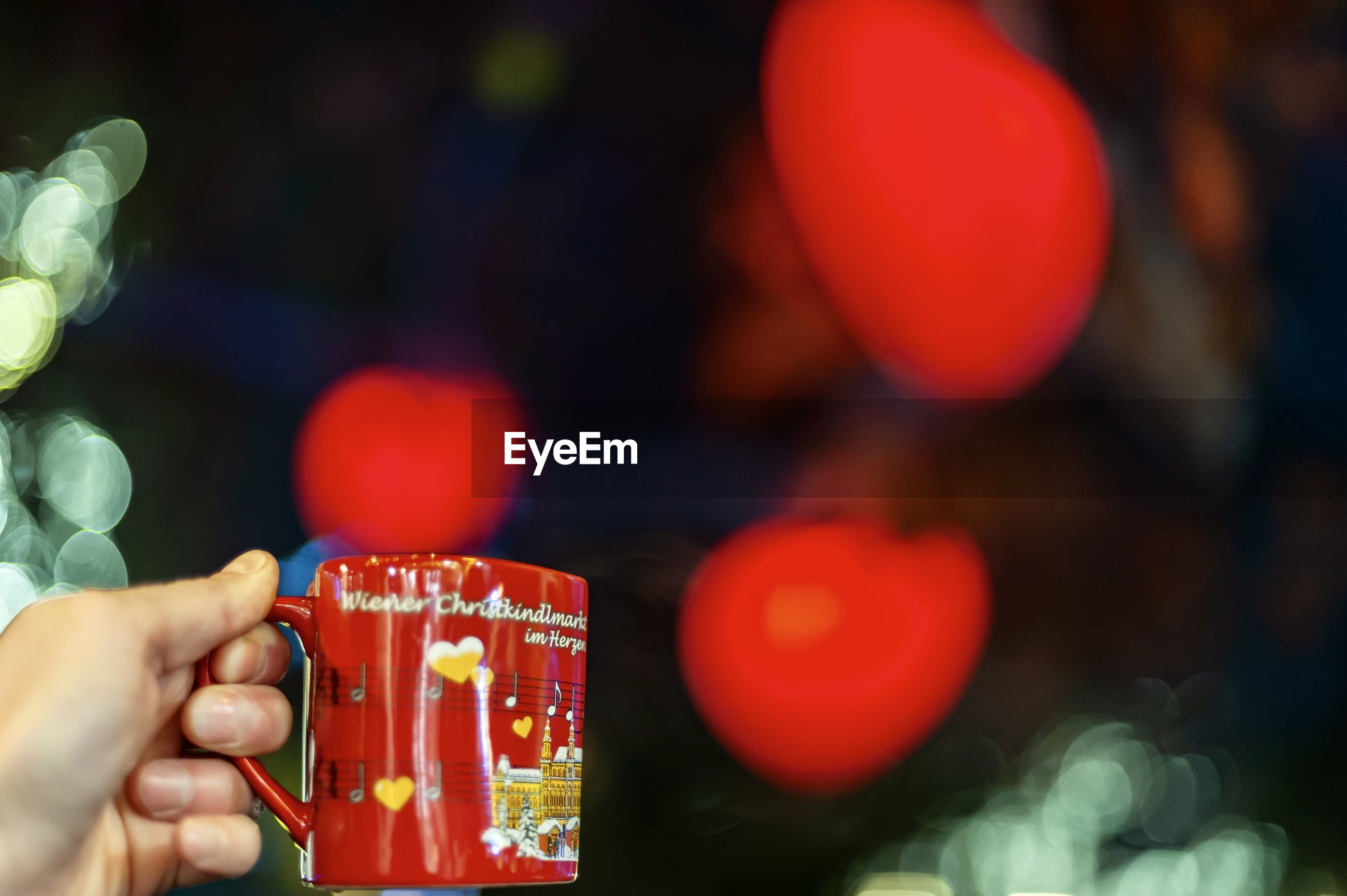 Close-up of hand holding coffee cup with text