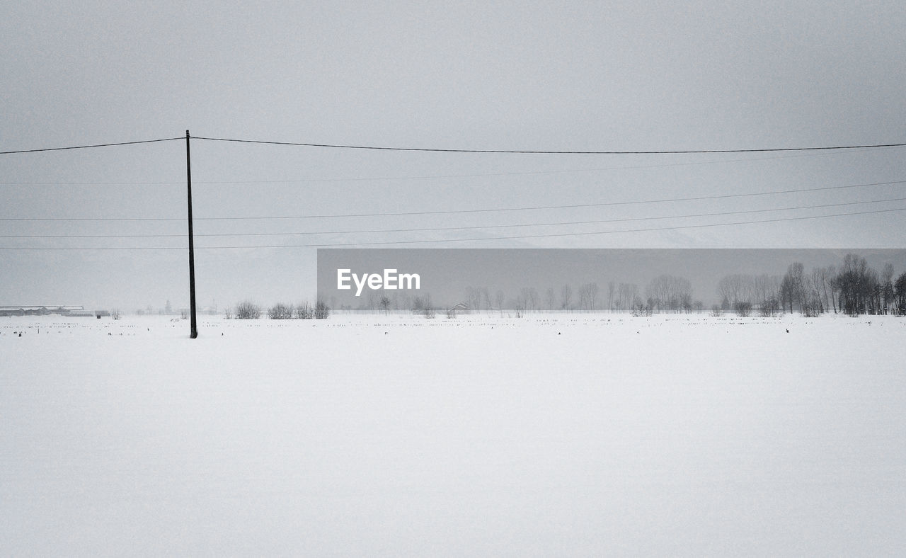 snow, cold temperature, winter, tranquility, tranquil scene, beauty in nature, environment, scenics - nature, sky, landscape, nature, covering, white color, cable, fog, no people, land, day, field, electricity, outdoors, extreme weather, snowcapped mountain, power supply, snowing