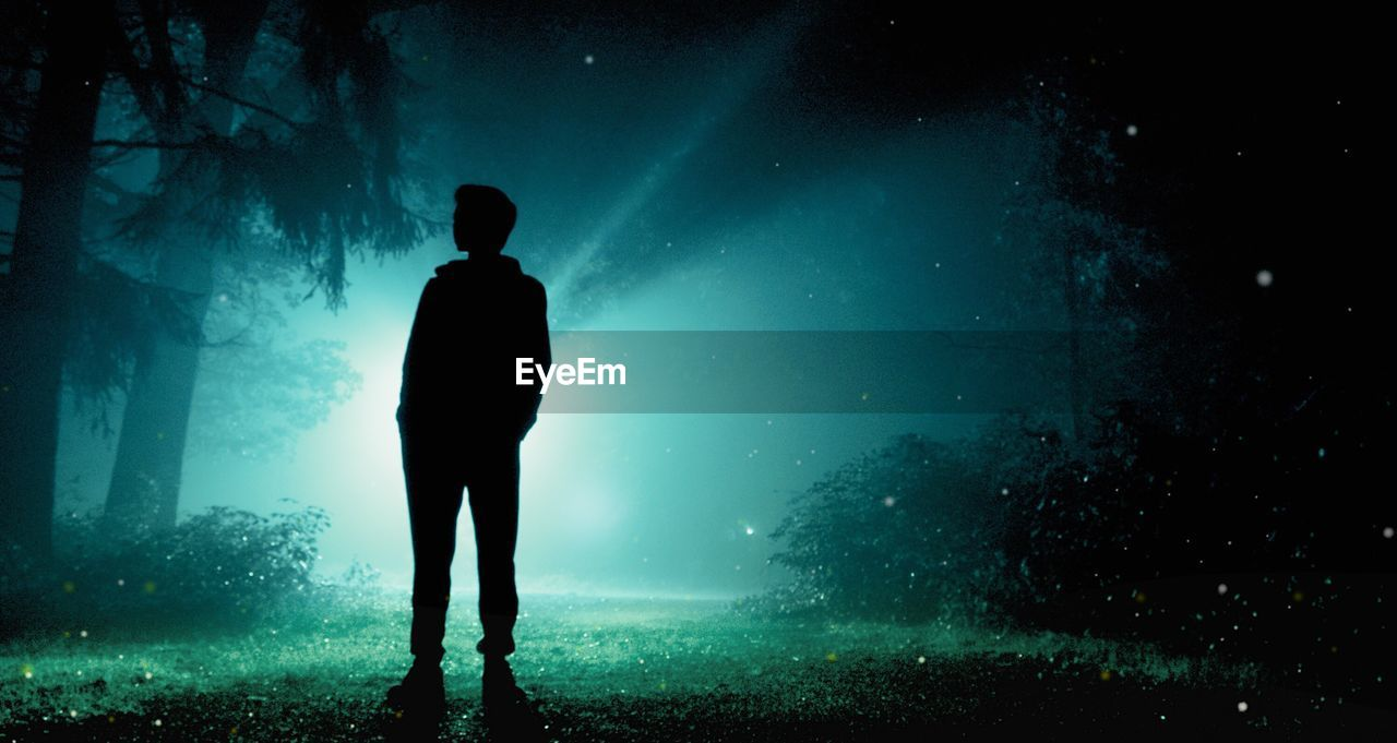 Full length of silhouette man standing on field at night