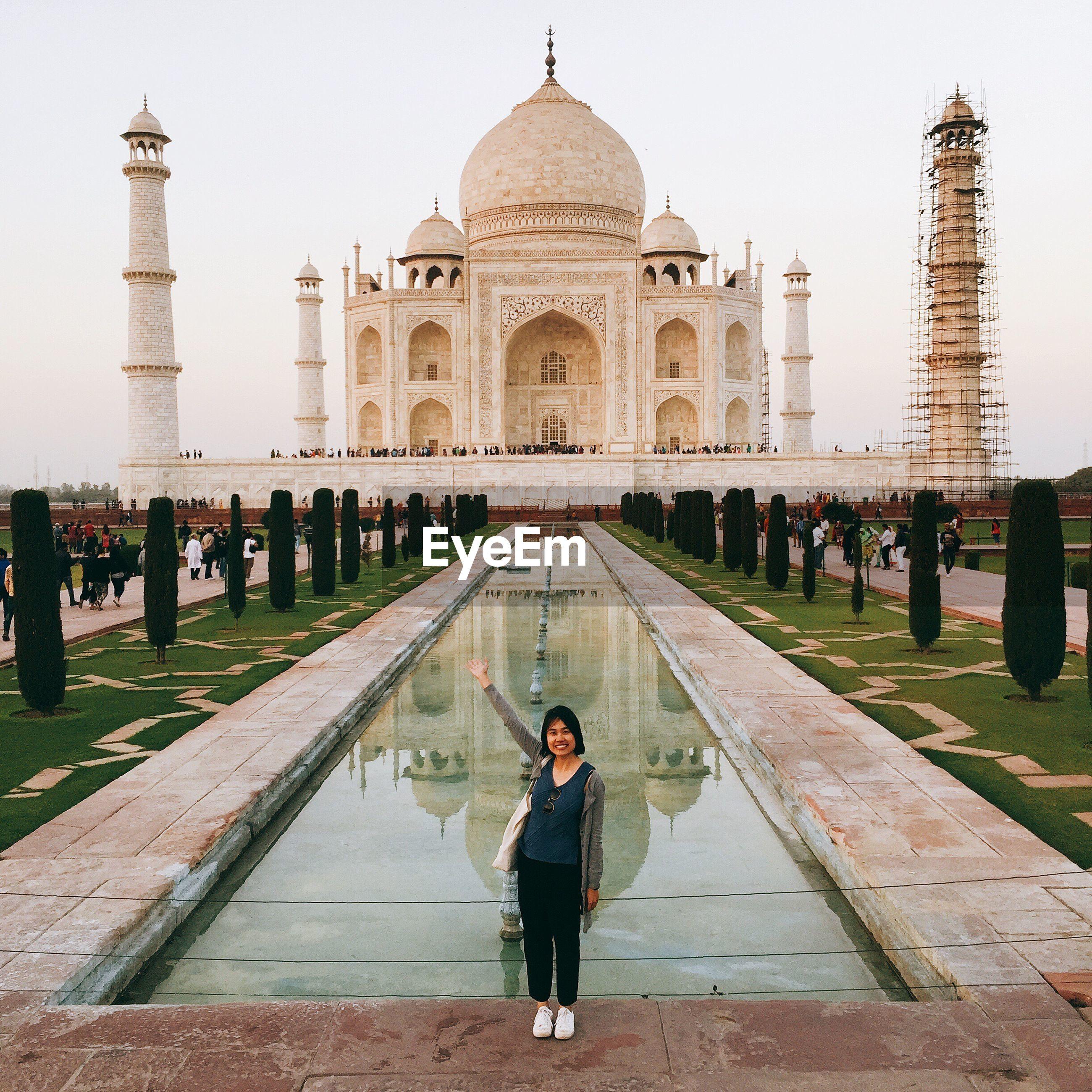 Full length of happy woman gesturing at taj mahal