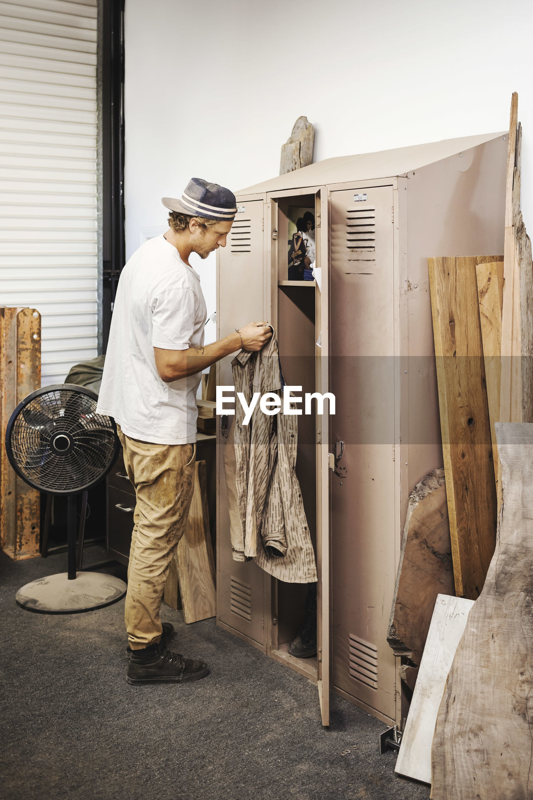 SIDE VIEW OF MAN WORKING AT FACTORY