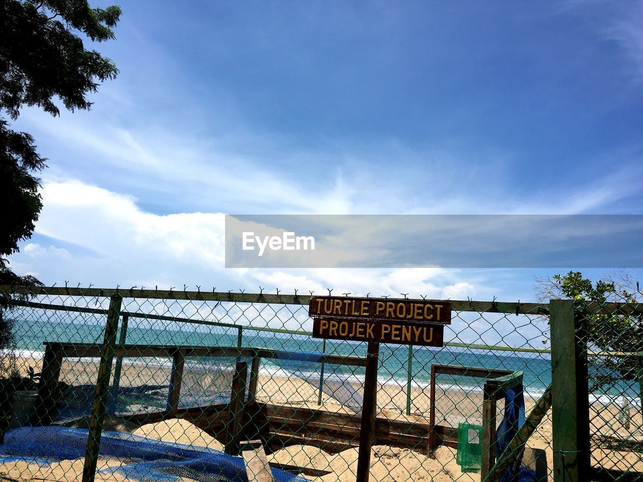 text, western script, sky, communication, day, outdoors, cloud - sky, nature, no people, beach, sea, tree, beauty in nature