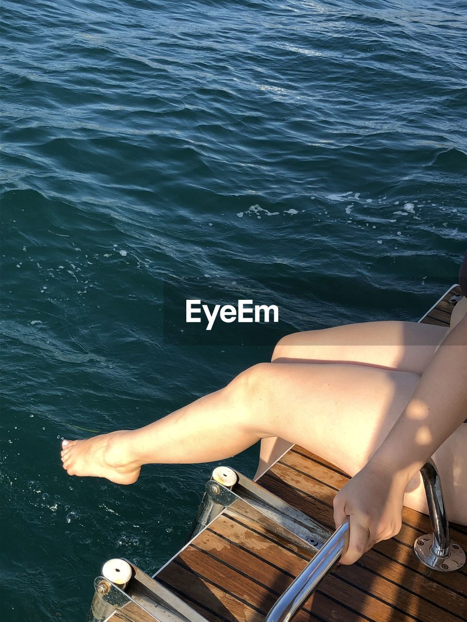 LOW SECTION OF WOMAN IN BOAT ON SEA