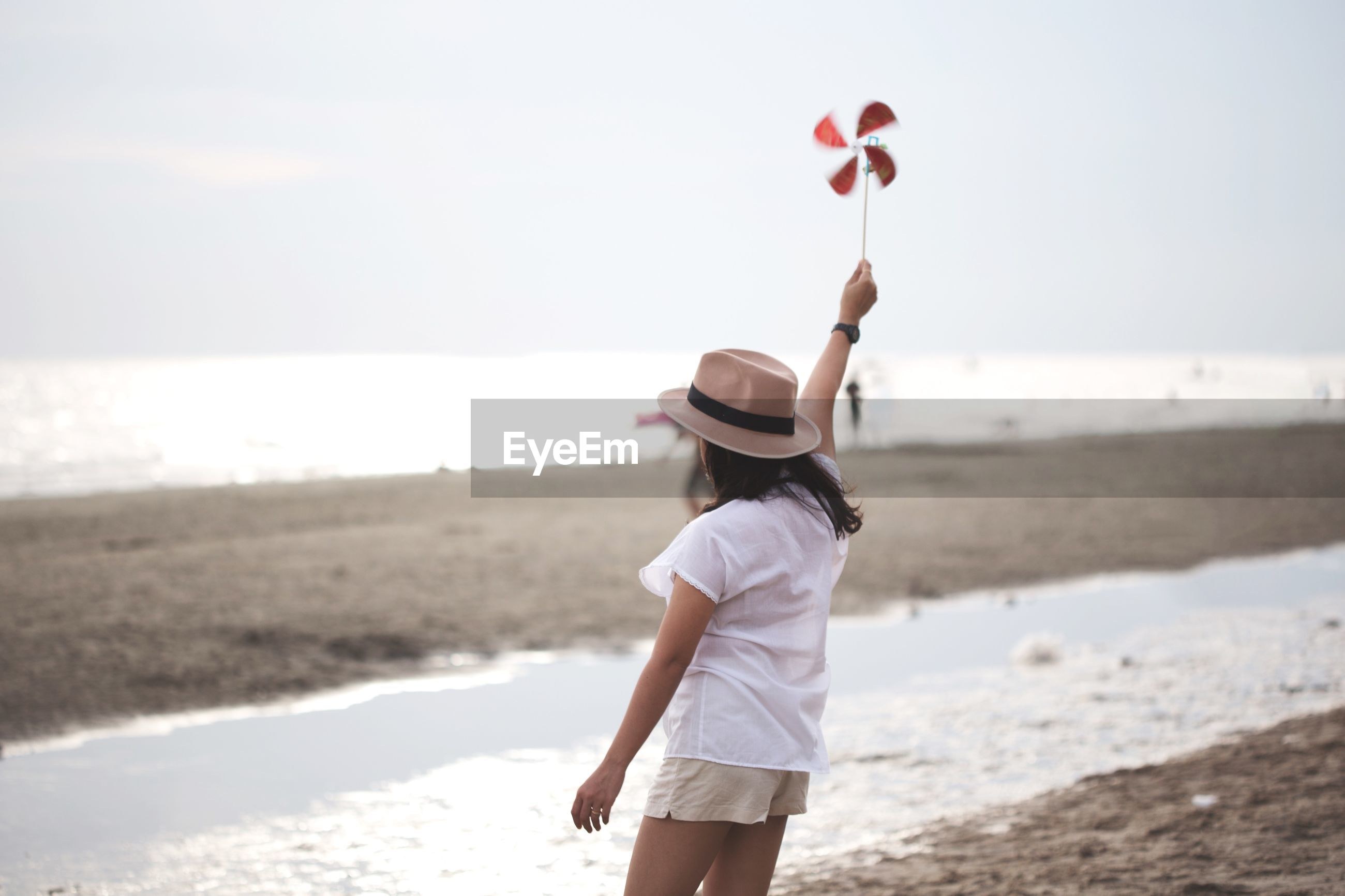Woman holding pinwheel toy while standing at beach against sky