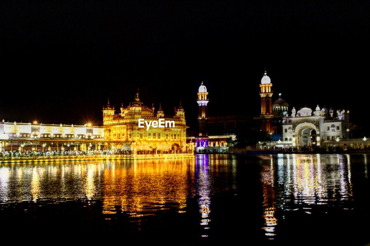 View of illuminated golden temple at waterfront