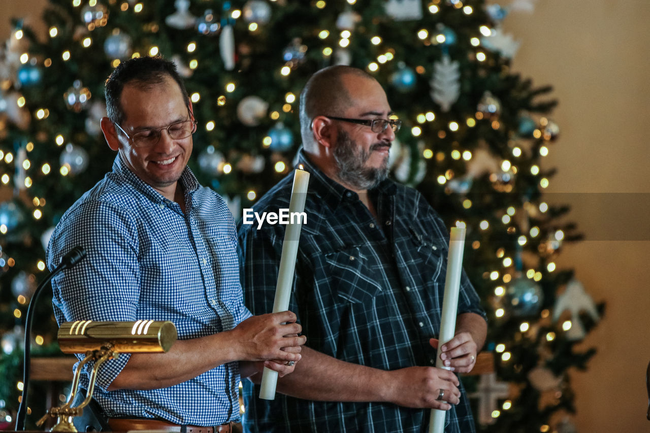 Men Holding Lit Candles By Christmas Tree