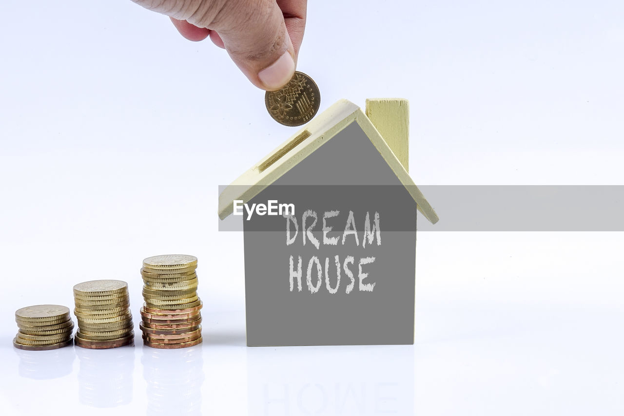 Close-up of hand holding coin over model home over white background