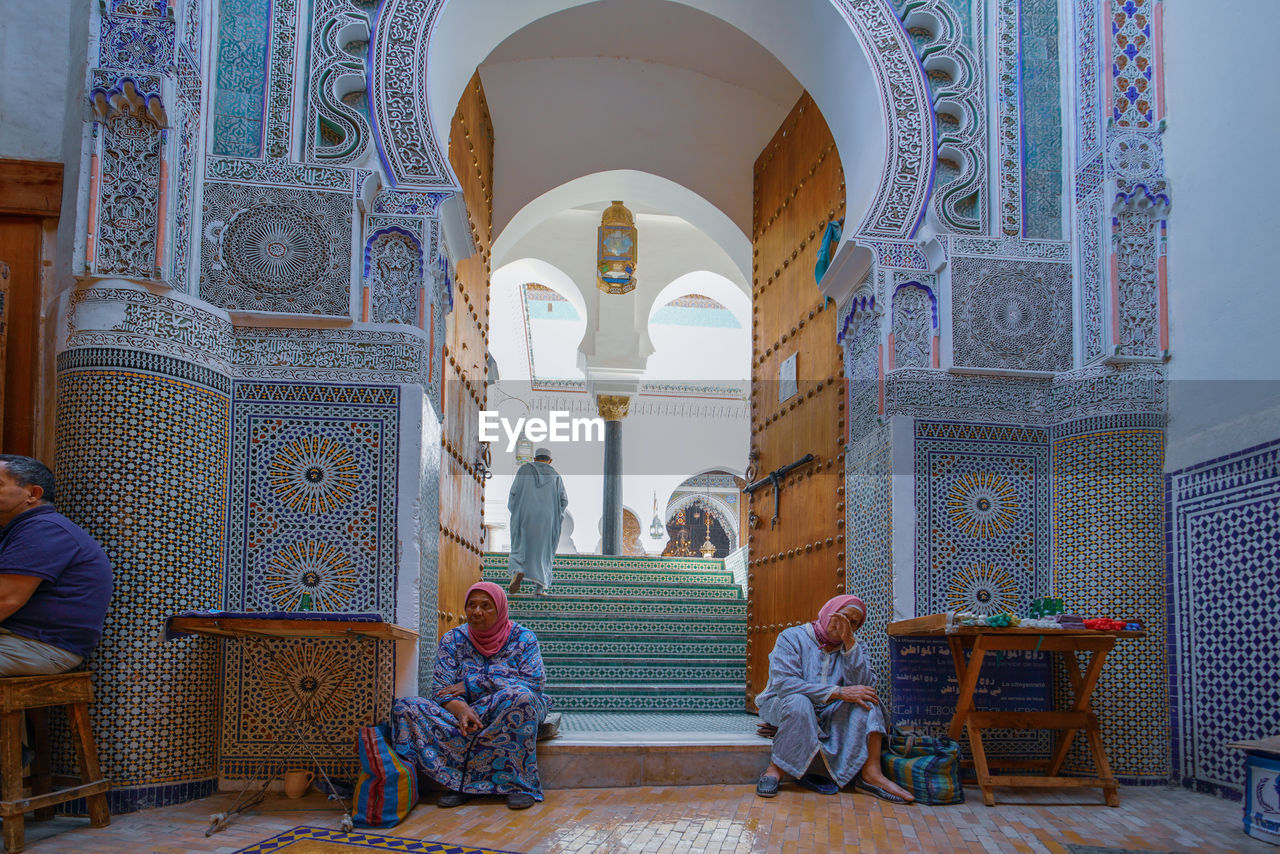 architecture, real people, built structure, building, arch, group of people, religion, women, men, place of worship, belief, adult, lifestyles, the past, spirituality, history, building exterior, people, rear view, architectural column